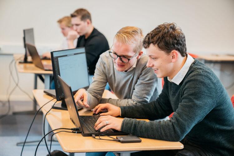 beeld studenten achter een laptop